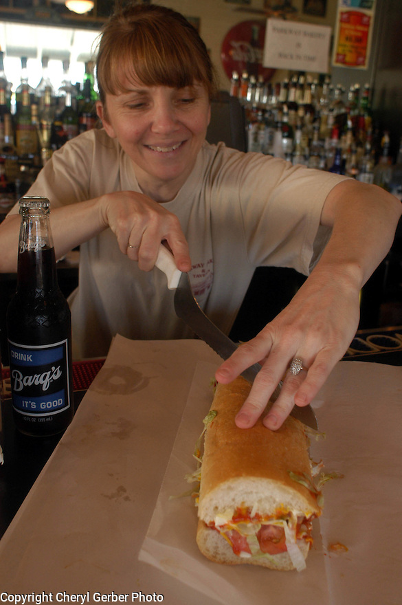 Parkway Tavern bartender Diane Daigle slices an oyster poboy for a customer dining at the bar, Wednesday, March 23, 2005..(Cheryl Gerber Photo)