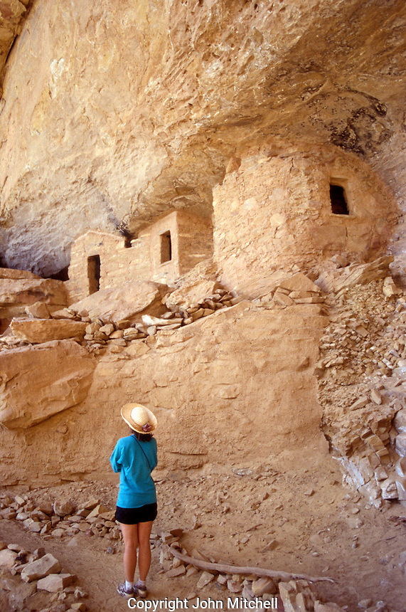 Young woman tourist looking at Anasazi cliff dwellings in Ute Mountain Tribal Park near Mesa Verde National Park, Colorado, USA