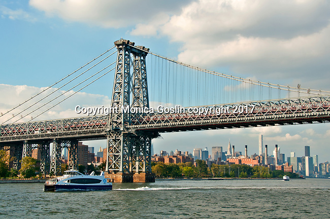 NY Waterway ferry boat on the East River with the Williamsburg Bridge and Manhattan skyline in the background