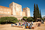 Fortified walls of the Alcazaba castle in the Alhambra complex, Granada, Spain with a group of school children in the foreground.