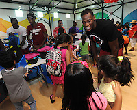 NWA Democrat-Gazette/ANDY SHUPE<br /> Moses Kingsley (right) smiles Wednesday, July 29, 2015, as he greets students as Manuale Watkins (from left) and Jimmy Whitt, all members of the University of Arkansas men's basketball team, hand out backpacks at the Boys and Girls Club of Fayetteville. The backpacks were filled with school supplies as needed, all provided by Dwelling Place Church, the Upsilon Chapter of Omega Psi Phi, the Gamma Eta Chapter of Omega Psi Phi, the Boys and Girls Club of Fayetteville, Walgreens, the University of Arkansas men's basketball team, and the Ronnie Brewer Foundation. After receiving a backpack and school supplies, the students spent time with the student-athletes and Brewer.