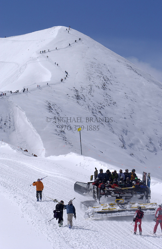 Skiers ride a snow cat as others hike their way to the top of Highland Bowl. Aspen Highlands ski area, Colorado. © Michael Brands. 970-379-1885. ski, skiing,