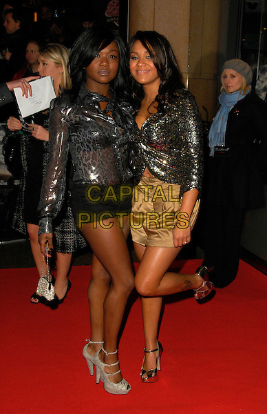 """BOOTY LUV - CHERISE ROBERTS & NADIA SHEPHERD.The UK film premiere of """"Beowulf"""", Vue Leicester Square, London, England..November 11th, 2007.full length silver grey gray top jacket gold skirt black shorts hotpants tattoo leopard print bag purse sequins sequined leg up .CAP/ CAN.©TCan Nguyen/Capital Pictures."""