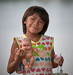 Luana Kanamari Bakero holds a doll in Atalaia do Norte, Brazil. The Kanamari indigenous girl painted the doll with her own tribe' facial markings. She and her mother came to visit Atalaia do Norte from their village several days upriver in a protected indigenous reserve.<br /> <br /> Written parental consent obtained.