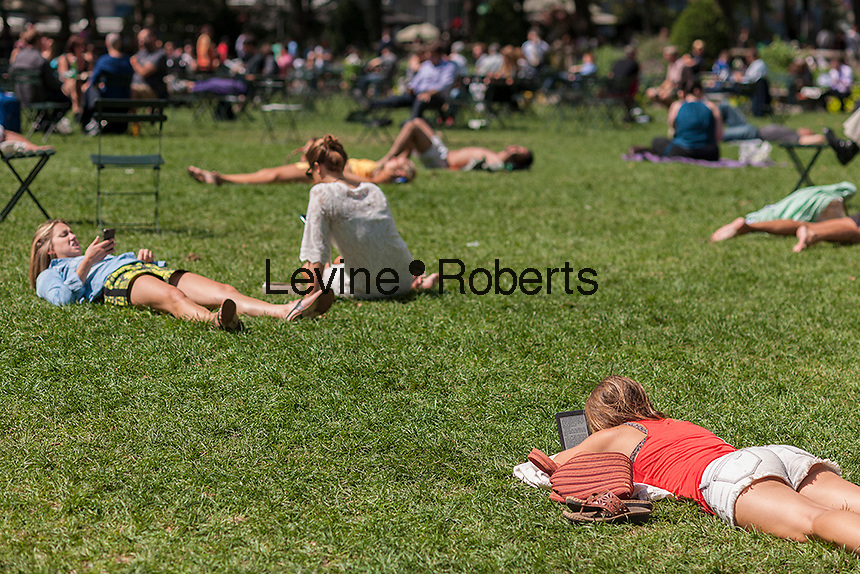 A visitor to Bryant Park in New York uses her Amazon Kindle on Thursday, August 15, 2013.  (© Richard B. Levine)