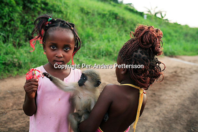 LUKUTU, DEMOCRATIC REPUBLIC OF CONGO MARCH 16: Unidentified girls play with their pet monkey on March 16, 2006 in Lukutu, Congo, DRC. Both girls traveled by boat from Kisangani to Kinshasa, a journey of about 1750 kilometers. About five hundred people traveled on the boat. Congo River is a lifeline for millions of people, who depend on it for transport and trade. During the Mobuto era, big boats ran by the state company ONATRA dominated the traffic on the river. These boats had cabins and restaurants etc. All the boats are now private and are mainly barges that transport goods. The crews sell tickets to passengers who travel in very bad conditions, mixing passengers with animals, goods and only about two toilets for five hundred passengers. The conditions on the boats often resemble conditions in a refugee camp. Congo is planning to hold general elections by July 2006, the first democratic elections in forty years..(Photo by Per-Anders Pettersson/Getty Images).
