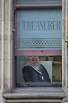 "© Joel Goodman - 07973 332324 . 23/10/2015 . Manchester , UK . A woman inside Manchester Town Hall by windows with "" TREASURER "" stencilled , as Chinese president , Xi Jinping , visits inside as part of his state visit to the United Kingdom . Photo credit : Joel Goodman"