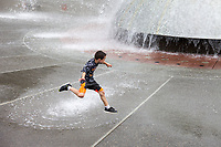 Boy jumping over water fountain spray, Northwest Folklife Festival 2016, Seattle Center, Washington, USA.