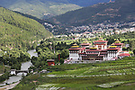 Tashichoi Dzong, the seat of government and spiritual Buddhism with the capital Thimpu behind...Bhutan the country that prides itself on the development of 'Gross National Happiness' rather than GNP. This attitude pervades education, government, proclamations by royalty and politicians alike, and in the daily life of Bhutanese people. Strong adherence and respect for a royal family and Buddhism, mean the people generally follow what they are told and taught. There are of course contradictions between the modern and tradional world more often seen in urban rather than rural contexts. Phallic images of huge penises adorn the traditional homes, surrounded by animal spirits; Gross National Penis. Slow development, and fending off the modern world, television only introduced ten years ago, the lack of intrusive tourism, as tourists need to pay a daily minimum entry of $250, ecotourism for the rich, leaves a relatively unworldly populace, but with very high literacy, good health service and payments to peasants to not kill wild animals, or misuse forest, enables sustainable development and protects the country's natural heritage. Whilst various hydro-electric schemes, cash crops including apples, pull in import revenue, and Bhutan is helped with aid from the international community. Its population is only a meagre 700,000. Indian and Nepalese workers carry out the menial road and construction work.