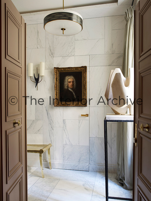 A jib door is concealed in the trompe l'oeil paint effect on the walls of the entrance hall