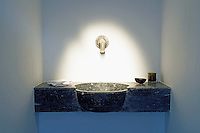 A 19th century basin constructed from a single piece of stone sits under an 18th century brass tap in the attic bedroom
