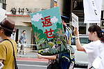 """Aug 6, 2011 - Tokyo, Japan - A protestor holds up a sign in Japanese saying """"Please give it back"""" during a anti-nuclear rally in the Shibuya district part of Tokyo: August 6 marks the 66th anniversary of the US atomic bombing of Hiroshima in 1945 as Japan still continues to struggle to end the nuclear crisis since the March 11 earthquake and tsunami. (Photo by Yumeto Yamazaki/AFLO)"""