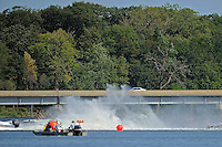 Frame 13: #37 Stacy Funk rolls over after contact with #31 Dan Schwartz (red and White boat with it's cowling in the air). Funk rolled completely over while it is speculated that Schwartz was knocked unconscious in the accident and accelerated across the river and crashed onto the golf course. In the later images of this series Schwartz can be seen emerging from behind Funk's boat. (SST-120 class)
