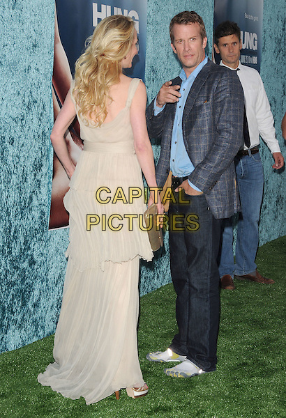ANNE HECHE & THOMAS JANE.The HBO Premiere of 2nd Season of Hung held at Paramount Picture Studios in Hollywood, California, USA..June 23rd, 2010.full length blue check shirt jacket suit white cream dress beige layers layered sheer gold clutch bag maxi jeans denim side back behind rear pointing finger .CAP/RKE/DVS.©DVS/RockinExposures/Capital Pictures.