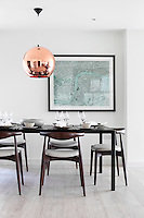 A round copper pendant light hangs above a dining table set for lunch with white tableware. The wood dining chairs are by Hans Wegner.