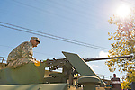 Bellmore, New York, U.S. 22nd September 2013. An Army soldier wearing camouflage uniform sits at machine gun at top of an armored tank at the Military Expo at the 27th Annual Bellmore Family Street Festival, featuring family fun with exhibits and attractions in a 25 square block area, with over 120,000 people expected to attend over the weekend.