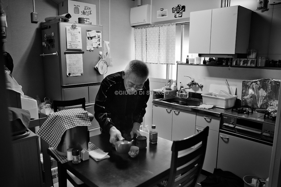life goes on in taro community, mr  Jan makes tea in his new temporary house, on  11th march 2012..In the north east of Japan there is a small city called Taro that was completely destroyed by the tsunami on the 3/11. After the tsunami the whole population of 8000 people moved to the top of the mountain where they settled down.  .Here they had temporary housing, temporary shops, a japanese warm bath and a temporary clinic provided by MSF. Almost one year later they are still living there, they have created their own new little community village and this has became the new reality for them. In this small colony you can find barber shops, restaurants, grocery stores, schools and a playground just like a normal village. The colony is not far from the sea so, as the majority of the population from Taro are fishermen, they don't find it too hard to survive in their new environment. From a temporary shelter this has became the new TARO Village.