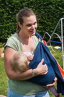 A mother breastfeeding in her garden with her baby in a sling.<br /> <br /> Taken: 01/05/2011<br /> Hampshire, England, UK
