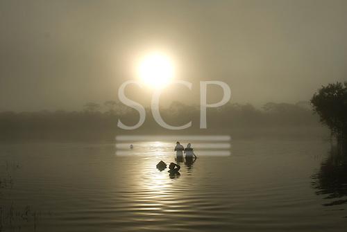 Xingu Indigenous Park, Mato Grosso State, Brazil. Aldeia Yawalapiti. People bathing in the morning mist.