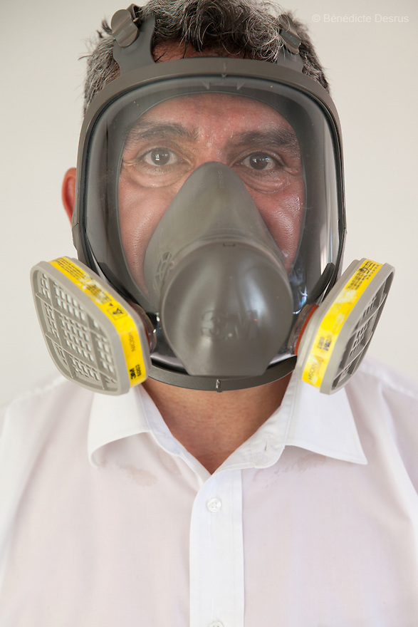 """Donovan wearing his ventilator mask after the cleanup of an unsolved homicide in Cuernavaca, Morelos – one of Mexico's most dangerous cities on August 7, 2015. The 66-year-old victim was a retired economics lecturer from the local university, and was killed in January of this year. The cleanup took place eight months later. The victim's family has since moved away to avoid further trouble. They remarked that justice is slow in Mexico and expressed dissatisfaction with the police investigation, but appreciated Donovan's discretion and professionalism. Donovan Tavera, 43, is the director of """"Limpieza Forense México"""", the country's first and so far the only government-accredited forensic cleaning company. Since 2000, Tavera, a self-taught forensic technician, and his family have offered services to clean up homicides, unattended death, suicides, the homes of compulsive hoarders and houses destroyed by fire or flooding. Despite rising violence that has left 70,000 people dead and 23,000 disappeared since 2006, Mexico has only one certified forensic cleaner. As a consequence, the biological hazards associated with crime scenes are going unchecked all around the country. Photo by Bénédicte Desrus"""