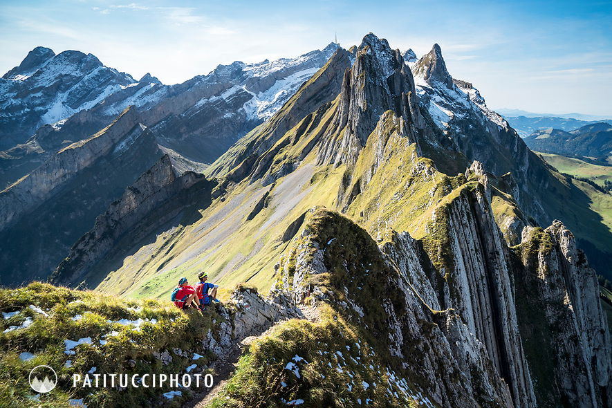 Two trail runners sit and relax next to the trailwhile on a running tour of the Alpstein mountains of eastern Switzerland.