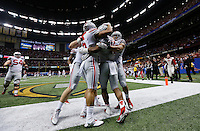 Teammates congratulate Ohio State Buckeyes running back Ezekiel Elliott (15) after he ran for an 85-yard touchdown in the fourth quarter of the Allstate Sugar Bowl college football playoff semifinal against the Alabama Crimson Tide at the Mercedes-Benz Superdome in New Orleans on Jan. 1, 2015. (Adam Cairns / The Columbus Dispatch)