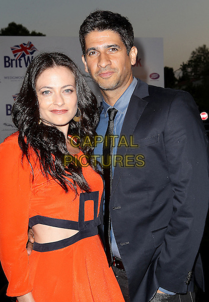 "Lara Pulver, Raza Jaffrey.7th Annual BritWeek Festival ""A Salute To Old Hollywood"" Launch Party held at the British Consul General's Residence, Los Angeles, California, USA..April 23rd, 2013.half length red orange dress black trim cut out away grey gray suit blue shirt tie couple .CAP/ADM/KB.©Kevan Brooks/AdMedia/Capital Pictures"