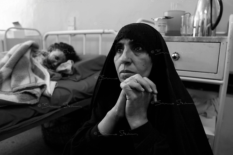 Baghdad, Iraq,  April 1, 2003.Yarmouk Hospital. Zuhama Abdel Mahmoud, right, watches over her niece Azzra Ismail, 6 who has been badly burned to the face and may have lost an eye  in the explosion of a US cluster bomb near her home in Southern Baghdad, 7 members of her family were killed.