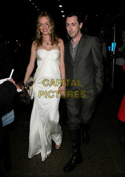 "HEATHER GRAHAM & ALAN CUMMING.UK Premiere of ""Elizabeth - The Golden Age"" at the Odeon Leicester Square, London, England, October 23rd 2007..full length white cream strapless dress holding hands grey suit black knee high riding boots.CAP/AH.©Adam Houghton/Capital Pictures."