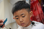 Kaohsiung, MegaPort Music Festival -- Young boy getting a haircut at the festival.