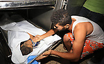 A relative mourns over the body of a Palestinian boy from the Baker family, whom medics said was killed with other three children from the same family by a shell fired by an Israeli naval gunboat, at a hospital morgue in Gaza City July 16, 2014. Four Palestinian children were killed and one was critically wounded on a Gaza beach on Wednesday by the shell fired by the Israeli naval gunboat, a Palestinian health official said. Asked about the incident, an Israeli military spokesman in Tel Aviv said he was checking the report. Gaza health officials said 213 Palestinians, most of them civilians, had been killed in air and naval barrages, in the worst flareup of Israeli-Palestinian violence in two years. One Israeli has been killed by shelling from Gaza that has made a race to shelter a daily routine for hundreds of thousands in Israel. Photo by Mohammed Asad