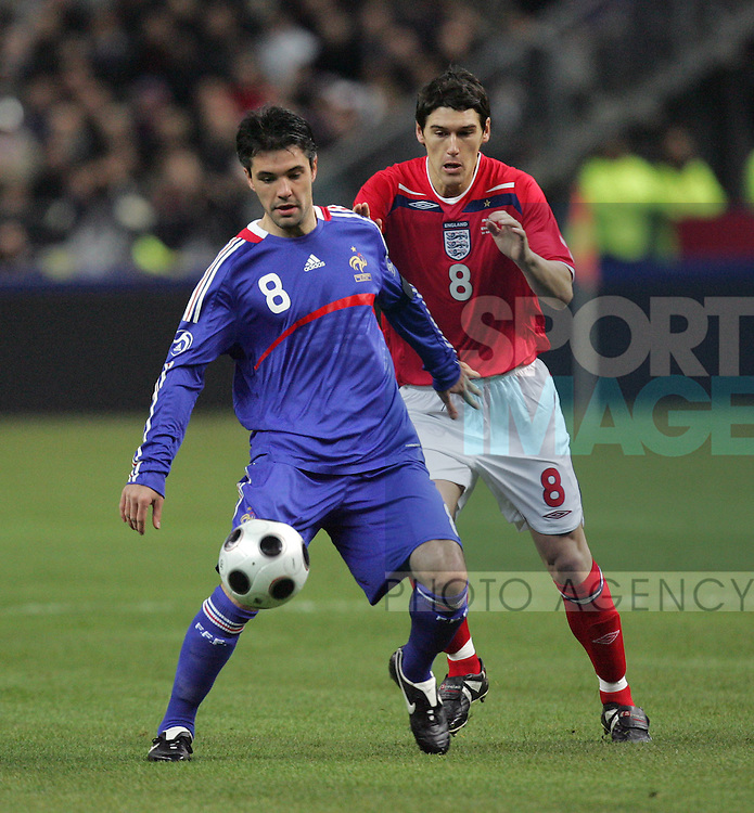 England's Gareth Barry tussles with France's Jeremy Toulalan