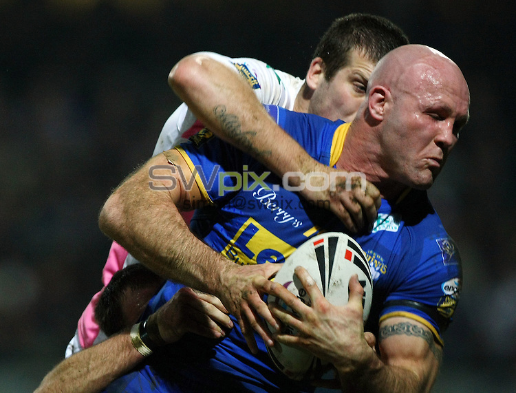 PICTURE BY VAUGHN RIDLEY/SWPIX.COM...Rugby League - Super League - Leeds Rhinos v Harlequins RL - Headingley, Leeds, England - 25/02/11...Leeds Keith Senior is tackled by Harlequins Tony Clubb.