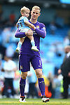 Joe Hart of Manchester City with his son during the lap of appreciation during the Barclays Premier League match at the Etihad Stadium. Photo credit should read: Philip Oldham/Sportimage