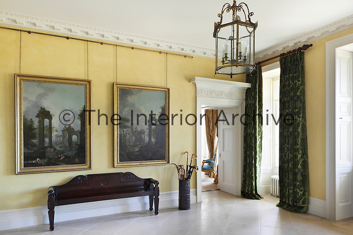 The yellow walls of the drawing room are echoed in the entrance hall, which is furnished with robust Irish Georgian furniture