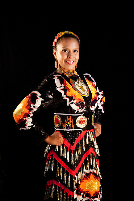 Jingle dancer Elishia Lahr (Navajo) wears a traditional jingle dress next to a black background