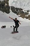 Man snowboarding in the Alps above Lauterbrunnen, Switzerland.