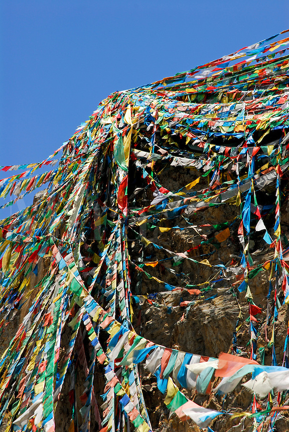 Prayer flags stream from Chagpo Ri, Iron Mountain, on the Lingkhor, a pilgrim circuit that encompasses the old city, Lhasa, Tibet, China.