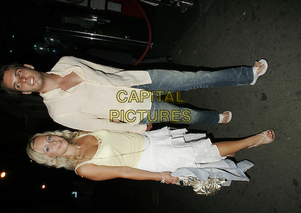 LEANNE WILSON & BOYFRIEND.Leaving a Celebrity Party at Pop Nightclub, .London, June 27th 2005..full length couple white layered ruffle skirt yellow vest top holding hands.Ref: SW.www.capitalpictures.com.sales@capitalpictures.com.©Stephen Walters/Capital Picture.