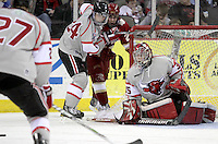 UNO goalie Fredrik Bergman eyes a loose puck as Bryce Aneloski holds back Denver's Nick Shore during the third period. Denver beat Nebraska-Omaha 4-2 Saturday night at Qwest Center Omaha. (Photo by Michelle Bishop)