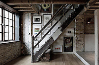 Art and photographs by friends of the owners decorate the walls of the staircase leading up to the living room and kitchen