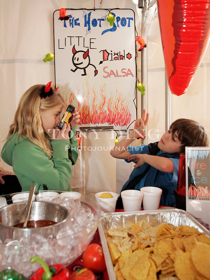 Northville children, eight year old Mina Plachta (left) and her six year old brother Mario, take pictures of themselves behind their family's salsa sampling table at the inaugural Fire and Ice Festival on Saturday, January 28, 2006 in Northville, MI. Local families and restaurants competed in a chili and salsa cookoff. TONY DING/Special to the Free Press