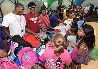 NWA Democrat-Gazette/ANDY SHUPE<br /> Manuale Watkins (from left) Jimmy Whitt and Moses Kingsley, all members of the University of Arkansas men's basketball team, laugh Wednesday, July 29, 2015, with students as they hand out backpacks at the Boys and Girls Club of Fayetteville. The backpacks were filled with school supplies as needed, all provided by Dwelling Place Church, the Upsilon Chapter of Omega Psi Phi, the Gamma Eta Chapter of Omega Psi Phi, the Boys and Girls Club of Fayetteville, Walgreens, the University of Arkansas men's basketball team, and the Ronnie Brewer Foundation. After receiving a backpack and school supplies, the students spent time with the student-athletes and Brewer.