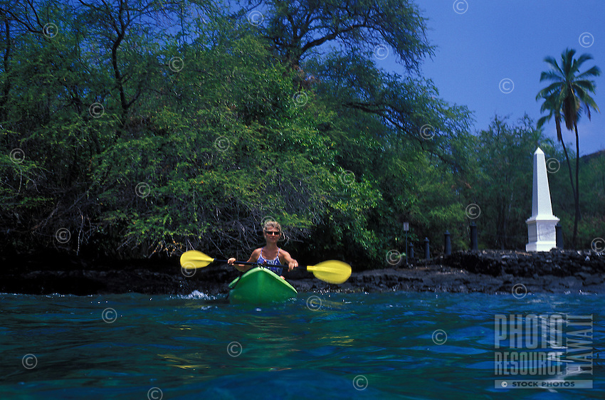 Woman kayaking in Kealakekua bay with Captain Cook monument in rear, Big island As of 2013 a moratorium halting all kaying in the bay has been issued by the Dept. of Land and Natural Resources. This could be revoked at anytime.