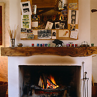 An assortment of family photos and memorabilia is tacked to the wooden frame of the large mirror which hangs above the fireplace in the living room