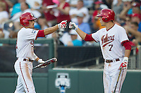 Indiana Hoosiers outfielder Wil Nolden (11) is greeted by teammate Michael Basil (7) after he scored against the Mississippi State Bulldogs during Game 6 of the 2013 Men's College World Series on June 17, 2013 at TD Ameritrade Park in Omaha, Nebraska. The Bulldogs defeated Hoosiers 5-4. (Andrew Woolley/Four Seam Images)
