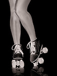 Closeup of sexy young woman legs wearing classic retro roller skates isolated on black background, artistic conceptual photo.