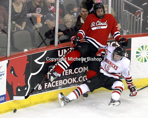 St. Cloud State's Kevin Gravel and UNO's Josh Archibald collide while fighting for the puck. Nebraska-Omaha defeated St. Cloud State 4-3 Saturday night at CenturyLink Center in Omaha. (Photo by Michelle Bishop) .