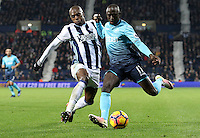 Modou Barrow of Swansea City FC looks to cross the ball into the box under the pressure of Allan Nyom of West Bromwich Albion during the Premier League match between West Bromwich Albion and Swansea City at The Hawthorns, England, UK. Wednesday 14 December 2016