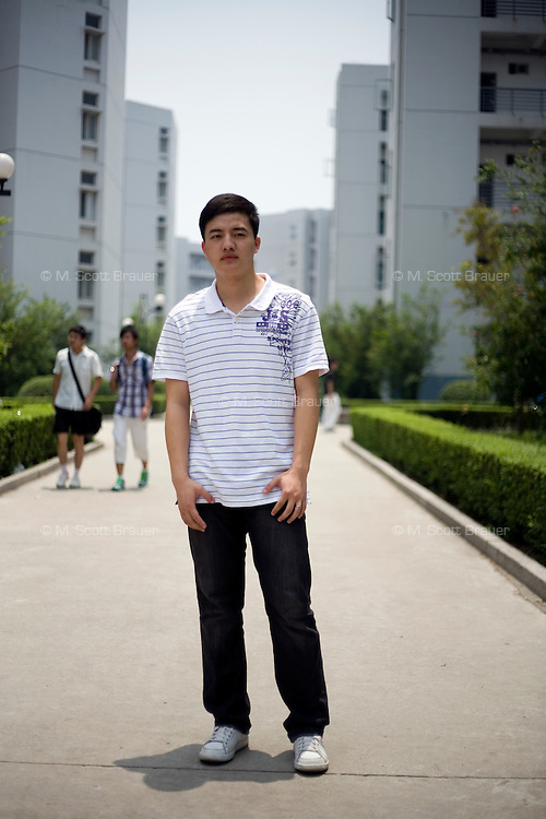 Liuwei, a student, age 23, poses for a portrait in Nanjing. Response to 'What does China mean to you?': 'I believe that China represents a lively and wonderful family. China is a country with a long history. China represents a peaceful and friendly family.'  Response to 'What is China's role in the future?': 'China has a large population, it is a large country. China has already taken large steps towards development. I believe China will become the global mainstream.'